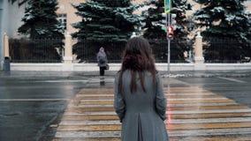 tillbaka sikt Den ledsna unga brunettflickan väntar klartecknet för att korsa vägen i vintern snö-täckt stad royaltyfri foto