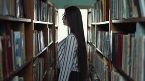 Tillbaka sikt för kontur som en härlig ung kvinna går mellan bokhyllorna i arkivet Begrepp: bildande lager videofilmer