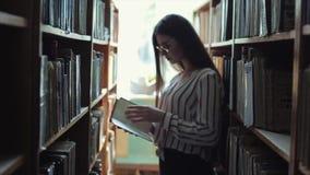 Tillbaka sikt för kontur som en härlig ung kvinna går mellan bokhyllorna i arkivet Begrepp: bildande stock video