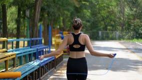 Tillbaka sikt på den unga idrottsman nen Woman i bekvämt rep för sportdräktbanhoppning på ett sportfält i parkera lager videofilmer