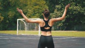 Tillbaka sikt på den unga idrottsman nen Woman i sportdräkten som är förlovad i kondition på sportfältet i parkera arkivfilmer