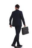 Tillbaka siktsbild av en affärsman som går med portföljen royaltyfria foton