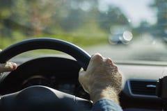 Tillbaka siktscloseup av en man som kör en modern bil arkivbild