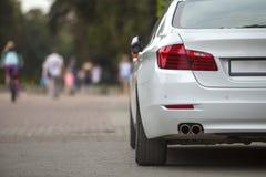 Tillbaka siktsdel av den vita bilen som parkeras på fot- zontrottoar för stad på bakgrund av suddiga konturer av cyklist- och fol royaltyfria bilder