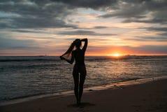 Tillbaka siktskontur av den sexuella kvinnan Härlig ung flicka med långt hår som går på stranden som poserar på solnedgången Fotografering för Bildbyråer