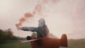 Tillbaka siktsliten flicka som kör i rolig plan pilot- dräkt med rök för röd färg i händer på solnedgångfältultrarapid stock video