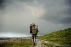 Tillbaka siktsman som går med en fotvandra ryggsäck på kusten royaltyfri fotografi