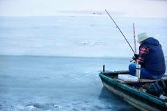 Tillbaka siktsnolla-fiskare i fartyg, medan fiska i vinter Arkivbild