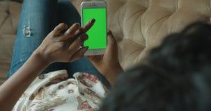 Tillbaka siktsslut upp afro- amerikansk kvinna ingen skärm för framsidamobiltelefongräsplan som surfar prata netto liggande Sofa  arkivfilmer