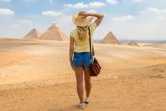 Tillbaka siktsst?ende av en enkel kvinna som h?ller ?gonen p? de stora pyramiderna av Giza royaltyfria foton
