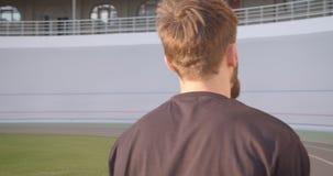 Tillbaka siktsstående för Closeup av den vuxna caucasian sportiga manliga joggeren som utomhus går på stadion i den stads- staden stock video