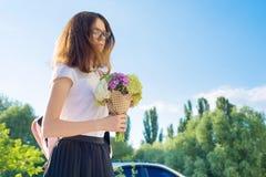tillbaka skola till Den ledsna tonåriga flickan går den första dagen till skolan, med ryggsäcken, blommor Royaltyfri Foto