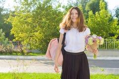tillbaka skola till Den lyckliga tonårs- flickan går den första dagen till skolan, med ryggsäcken, blommor Royaltyfri Foto
