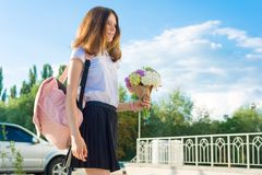 tillbaka skola till Den lyckliga tonårs- flickan går den första dagen till skolan, med ryggsäcken, blommor Royaltyfri Bild