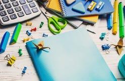 tillbaka skola till En blå anteckningsbok ligger på en vit tabell royaltyfria bilder