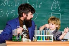 tillbaka skola till fader och son på skola skolaungeforskare som studerar vetenskap Liten unge som lär kemi i skola arkivfoton