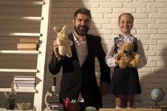 tillbaka skola till Flicka och hennes fader i klassrum på vit tegelstenbakgrund Royaltyfri Bild
