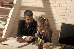 tillbaka skola till Flickan och mannen sitter på skrivbordet och ser in i mikroskopet royaltyfri fotografi