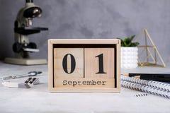 tillbaka skola till Grupp av skolatillförsel, mikroskopet och träkalendern med datumet 1st September Fotografering för Bildbyråer
