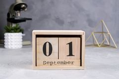 tillbaka skola till Grupp av skolatillförsel, mikroskopet och träkalendern med datumet 1st September Royaltyfria Bilder