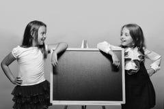 tillbaka skola till Ungar som bär skolakläder, lutar på den skinande svart tavla Arkivbild
