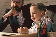 tillbaka skola till Ungen och mannen sitter vid skrivbordet med skolatillförsel Arkivfoto