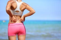 Tillbaka smärta - den idrotts- kvinnan som tillbaka gnider henne Fotografering för Bildbyråer