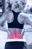 Tillbaka smärta - den idrotts- rinnande kvinnan med skada royaltyfria foton