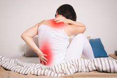 Tillbaka smärta, njureinflammation, kvinnalidande från ryggvärk hemma arkivbild