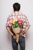 Tillbaka stilig ung man med skägget och den trevliga buketten av blommor Royaltyfri Fotografi