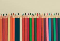 Tillbaka till skola, begrepp från kulöra blyertspennor på en gul bakgrund från texturerat papper för att skissa Tonat i ett moder arkivbild