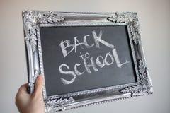 Tillbaka till skola, text p? den svart tavlan i en tappningram arkivfoton