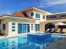 Tillbaka uteplats av den tropiska villan med den stora simbass?ngen royaltyfria foton