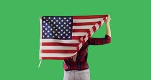 Tillbaka vuxen kvinna med amerikanska flaggan på den nyckel- gröna skärmen för chroma stock video