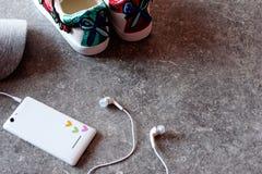Tillbehör för flicka` s - vit smartphone, hörlurar, gymnastikskor och grått lock arkivbild