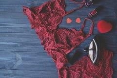 Tillbehör för kvinna` s på trätabellen Rött snöra åt damunderkläder royaltyfria foton