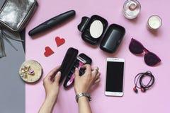 Tillbehör för lopp för kvinna` s, sommarhygienobjekt på en bakgrund för pastellfärgade rosa färger Semester- och loppobjekt Lekma royaltyfri fotografi