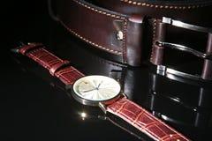 Tillbehör för man` s med den bruna det läderplånboken, bältet och klockan på svart spegelbakgrund Arkivbild