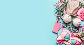 Tillbehör för sommarferie och lopp: sugrörhatten, kokosnötdrinkar, bikini, och ilar telefonen på turkosblåttbakgrund, bästa sikt royaltyfri foto