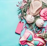 Tillbehör för sommarferie och lopp: sugrörhatten, kokosnötdrinkar, bikini, och ilar telefonen på turkosblåttbakgrund, bästa sikt royaltyfri fotografi
