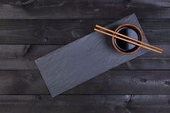 Tillbehör för sushi Soya pinnar på den svarta stenplattan Bästa sikt med kopieringsutrymme arkivfoto