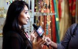Tillbehören för mode för kvinna för TV-kanalreporterintervju shoppar owne arkivfoto