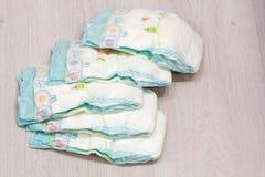 Tillbehöruppsättningen för Baby disponibla blöjor på grått bakgrundsträd, objekt för behandla som ett barn omsorg Lekmanna- blöja Royaltyfri Bild
