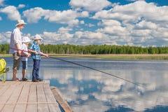 Tillbringa veckoslutet fadern och söner på den härliga sjön, faderteachen Royaltyfria Bilder