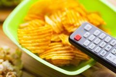 Tillbringa veckoslutet hemma, fritidlivsstilen, TV, snabbmatbegrepp royaltyfria foton