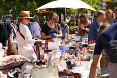 Tillbringa veckoslutet loppmarknaden i centret på en solig dag Marknadsbåset med till salu objekt och folket söker efter ett bra  arkivfoton