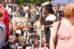 Tillbringa veckoslutet loppmarknaden i centret på en solig dag Marknadsbåset med till salu objekt och folket söker efter ett bra  arkivfoto