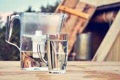Tillbringare för vattenfilter och en genomskinlig exponeringsglaskopp av rent vatten framme av träattraktionbrunnen utomhus i som arkivfoton