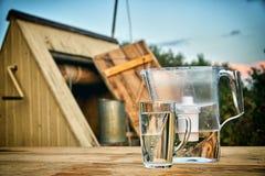Tillbringare för vattenfilter och en genomskinlig exponeringsglaskopp av rent vatten framme av träattraktionbrunnen utomhus i som arkivbild