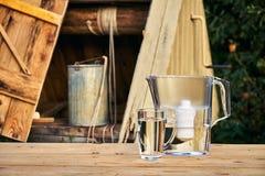 Tillbringare för vattenfilter och en genomskinlig exponeringsglaskopp av rent vatten framme av träattraktionbrunnen utomhus i som arkivbilder